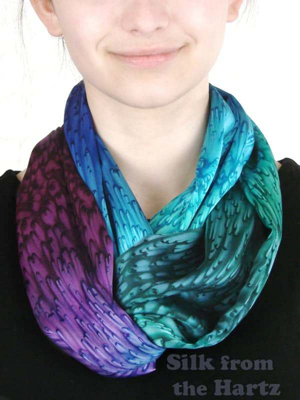 Rich beautiful colors of blue, green and purple hand dyed in a raindrop pattern on a silk satin infinity scarf, with a twist around the neck.