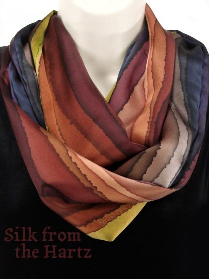 A unique fall color striped brown silk infinity scarf, looped around twice. Hand dyed by the artist in creative stripes of peach, denim, browns and greens. Made of luxuriously soft silk satin.