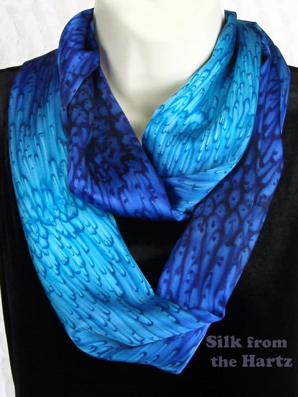 Royal blue, navy and turquoise hand dyed silk infinity loop scarf, draped around neck twice