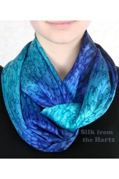 Royal blue silk satin eternity or infinity scarf twisted once around the neck.