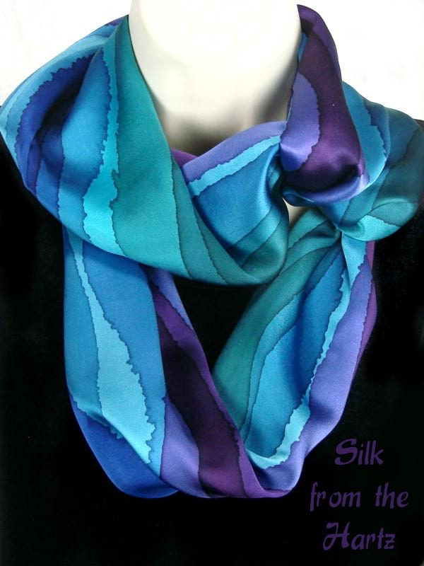 Jewel tone women's silk infinity scarf with unique and elegant hand painted stripes of blue, green and purple. Peacock color loop circle scarves for her.