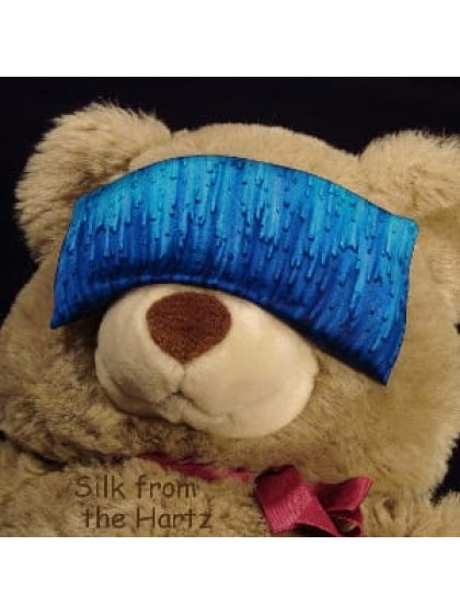 A blue hand dyed silk satin eye pillow on a stuffed bear, filled with flax and lavender for herbal aromatherapy.  An inexpensive luxury gift under $20 for relaxation, yoga, massage or sleep.