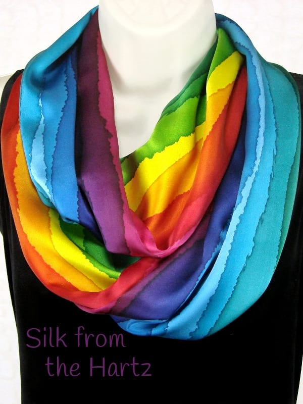 A colorful rainbow fashion silk infinity scarf, hand painted in stripes of red, yellow, green, blue and purple. Bright colors for summer or anytime.