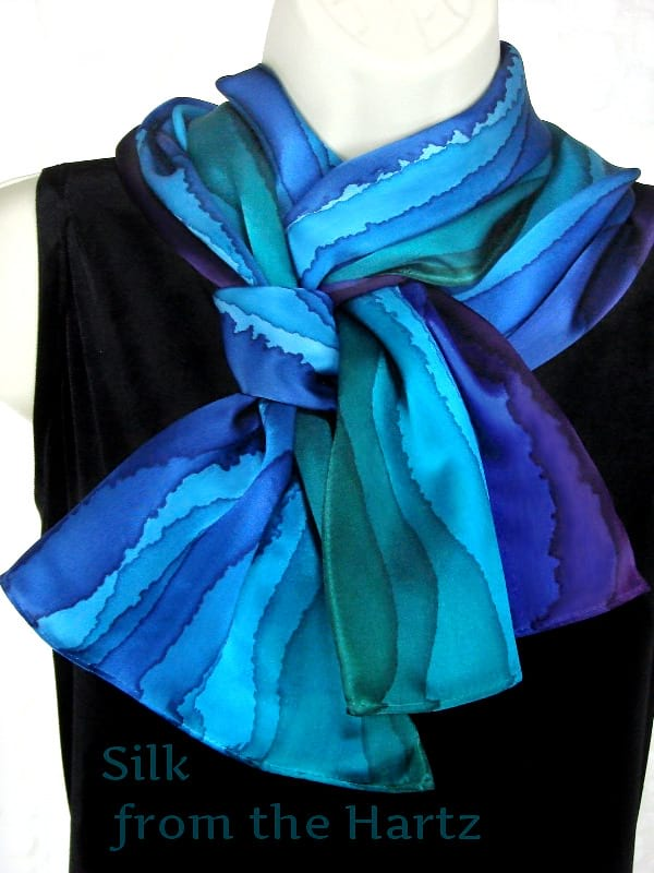 Unique blue green and purple stripe design hand painted luxuriously soft silk satin scarf for women tied in a braid pattern around the neck.