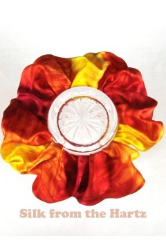 A Colorful yellow red silk hair scrunchie hand made in the USA