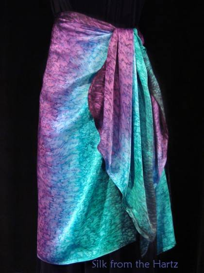 Jewel tone travel cruise wear silk sarong swimsuit coverup in blue, green and purple tied around the waist.