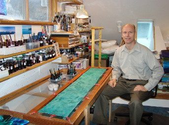 Silk artist Warren Hartz in his studio with a silk scarf stretched on a frame.